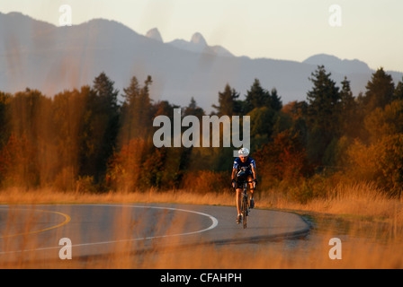 Man road cycling at Iona Beach Regional Park. Richmond, British Columbia, Canada - Stock Photo