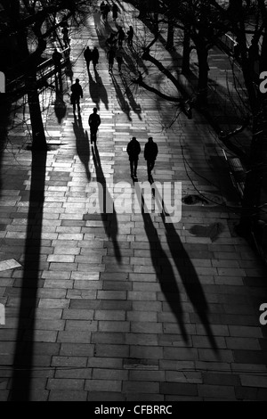 Shadows and silhouettes of pedestrians walking along the Queen's Walk alongside the River Thames at South Bank, - Stock Photo