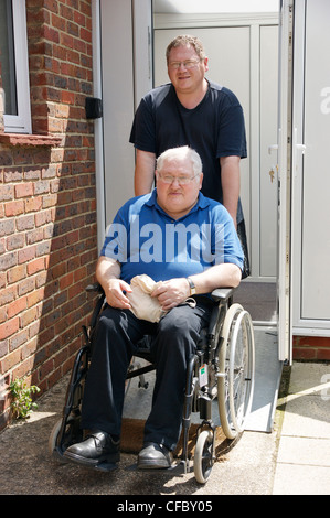 disabled elderly man in wheelchair with his carer son outside their front door - Stockfoto