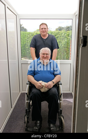 disabled elderly man in wheelchair with his carer son being pushed indoors from porch to hall - Stockfoto