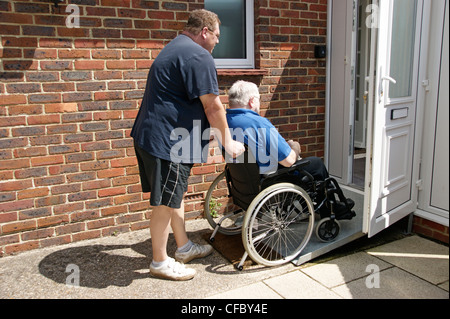 male carer / son pushing elderly man in wheelchair on ramp access to property - Stockfoto