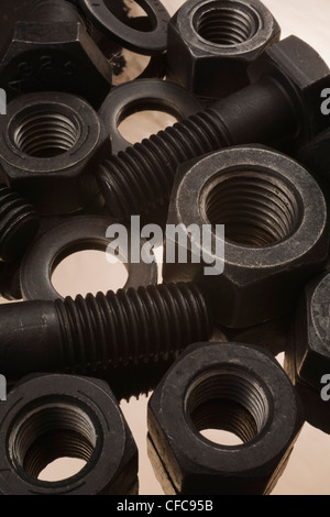 Large black steel bolts, nuts and washers on tin foil background - Stock Photo