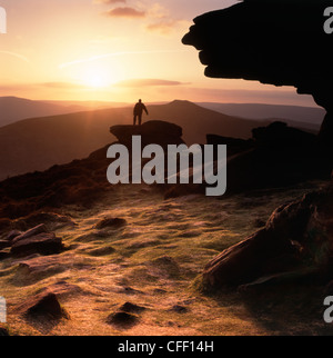 Lone male  walker stood on  rocks viewing the sunset at Bamford Edge in Derbyshire 'Great Britain' - Stock Photo