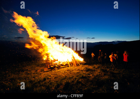 People at sacred heart fire in the evening, Val d'Ega, Karerpass, South Tyrol, Alto Adige, Italy, Europe - Stock Photo