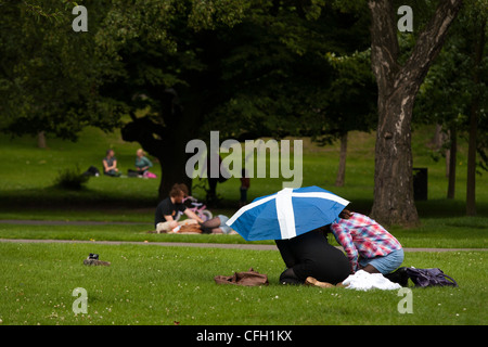 A couple hiding under an umbrella with the Scottish flag decorating it in Kelvingrove park in Glasgow - Stock Photo