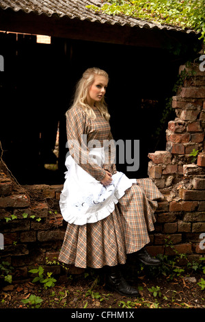 Blond girl in period servant dress - Stock Photo