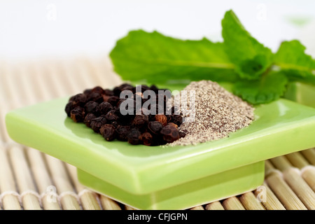 peppercorns and ground pepper on green ceramic dish - Stock Photo