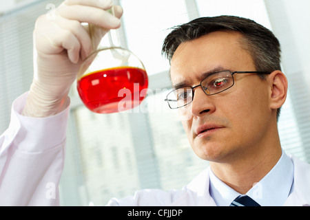 Serious clinician looking at flask with red liquid in laboratory - Stock Photo