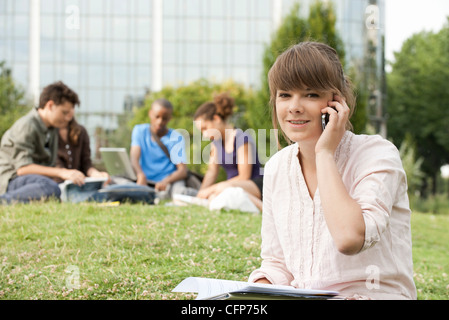 Young woman talking on cell phone, people in background, portrait - Stock Photo