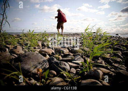 THIS IS A SELF PORTRAIT ON LAKE HURON. THIS IS A VERY ROCKY BEACH WITH GRASS SPROUTING UP EVERYWHERE. THIS IS EARLY - Stock Photo