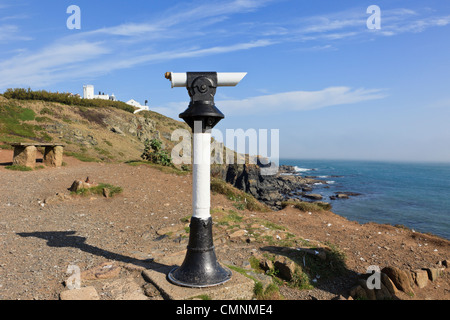Public telescope on peninsula clifftop looking out over Cornish coast with lighthouse beyond on Lizard Point Cornwall - Stock Photo