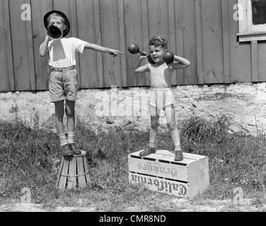 1930s 1940s BOYS PLAYING CARNIVAL STRONGMAN ONE LIFTING DUMBBELLS OTHER ANNOUNCING ACT THROUGH MEGAPHONE - Stock Photo