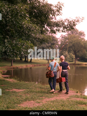 1970s TWO BOYS WALKING BESIDE POND CARRYING FISHING POLES AND TACKLE - Stock Photo