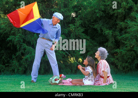 GRANDPARENTS AND GRANDDAUGHTER FLYING KITE ON PICNIC - Stock Photo