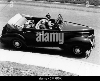1930s 1940s COUPLE HUSBAND AND WIFE DRIVING 1938 CONVERTIBLE FOUR DOOR SEDAN AUTOMOBILE WITH LUGGAGE IN BACK SEAT - Stock Photo
