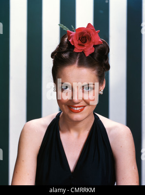 1940s 1950s PORTRAIT SMILING BRUNETTE TEENAGE GIRL WEARING BLACK EVENING GOWN LARGE RED ROSE IN HAIR LOOKING AT - Stock Photo