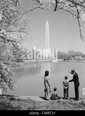 1960s FAMILY MOTHER FATHER TWO BOYS IN WASHINGTON DC LOOKING AT WASHINGTON MONUMENT AMID CHERRY BLOSSOMS - Stock Photo
