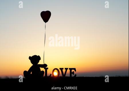 Teddy bear holding a heart shape balloon next too the word LOVE at sunrise - Stockfoto