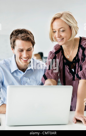 Two people using laptop and smiling - Stock Photo