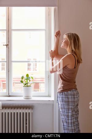 Woman opening window blind - Stock Photo