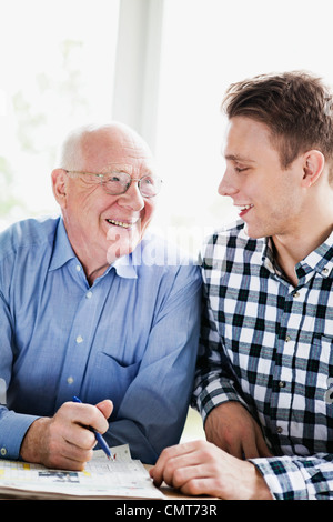 Happy senior man and grandson solving crossword - Stockfoto
