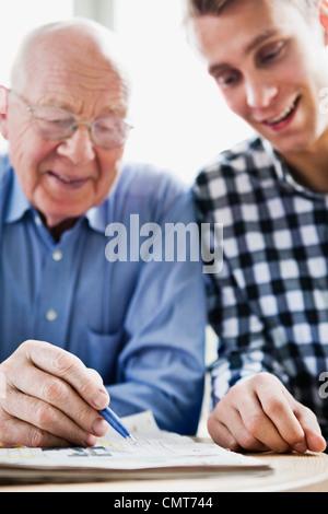 Guy and elderly man solving crossword - Stock Photo