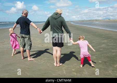 Rear view of parents and daughters (4-7) holding hands on beach - Stock Photo