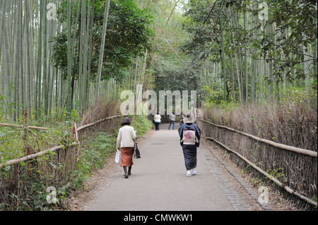 Japanese women walking through bamboo forest in Arashiyama, Kyoto, Japan - Stock Photo