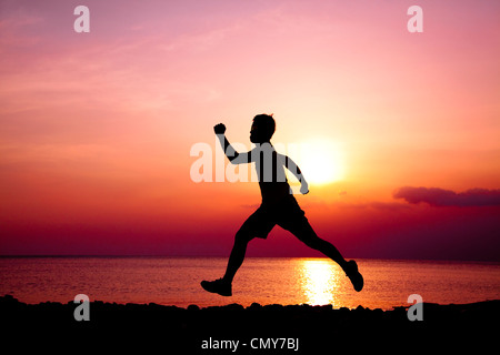 The Silhouette of runner on the beach - Stock Photo