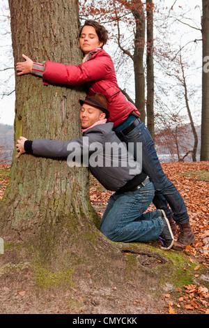 Germany, Berlin, Wandlitz, Couple hugging tree - Stock Photo