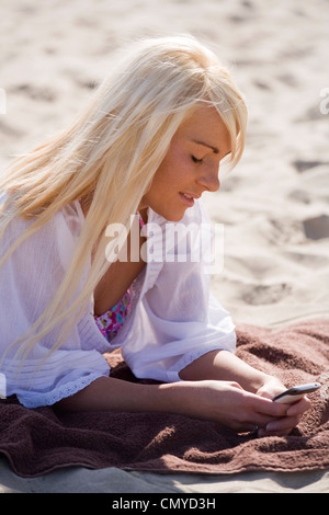 Pretty blonde woman on a beach holding a mobile phone. - Stock Photo