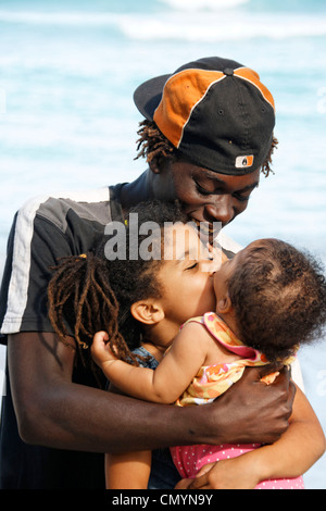 Jamaica Boston bay Jamaican father with kids kissing each other - Stock Photo