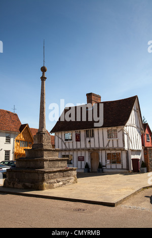 The stone cross in Lavenham Market Place with medieval buildings around, Lavenham, Suffolk - Stock Photo