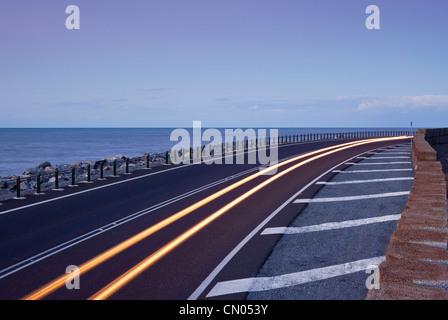 Car light trails on coastal highway.  Captain Cook Highway between Port Douglas and Cairns, Queensland, Australia - Stockfoto