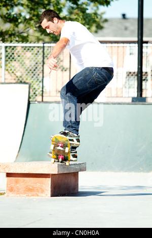Skateboarder grinding on ledge in skatepark - Stock Photo