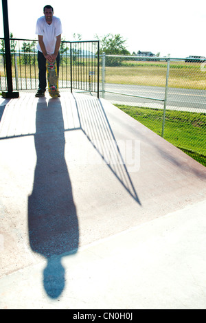 Skateboarder standing on ramp with large shadow - Stock Photo