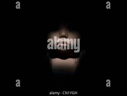 Doll's face in darkness, close up - Stock Photo