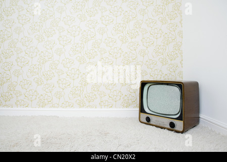 Retro television in corner of room with patterned wallpaper - Stockfoto