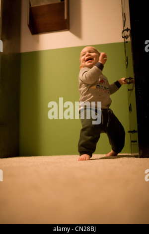 Toddler boy taking first steps - Stock Photo