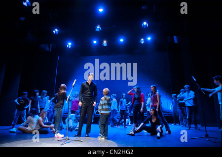 A group of boys and girls, teenagers singing and dancing in a amateur musical theatre performance production in - Stock Photo