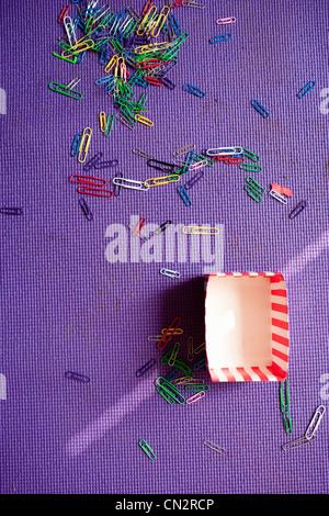 Paper clips on purple carpet - Stock Photo