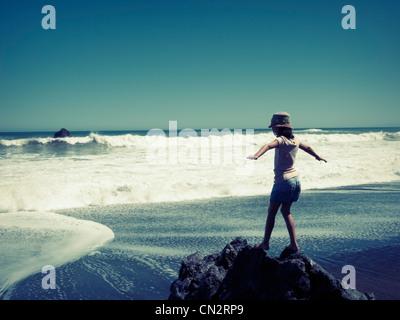Girl rides rock, Southern Ocean, New Zealand. - Stock Photo
