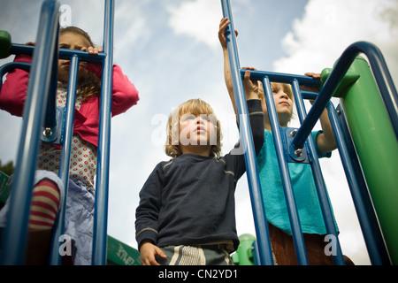 Three children in playground - Stock Photo