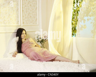 Portrait of a young pregnant woman at the window - Stock Photo