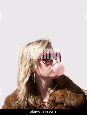Woman blowing bubble gum - Stock Photo