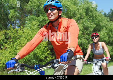 Portrait of a handsome man riding a bike with his wife on background - Stock Photo