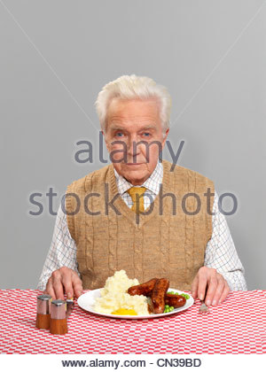 Senior man with sausages and mash - Stock Photo