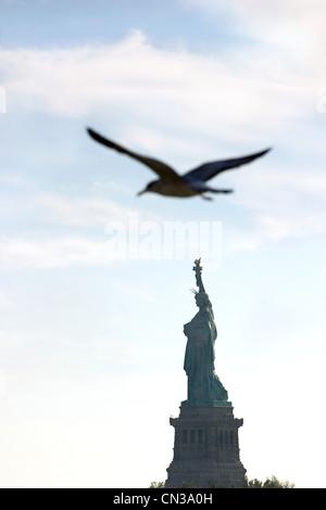 Bird flying over Statue of Liberty, New York - Stock Photo