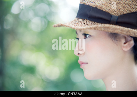 Young woman wearing straw hat, portrait - Stock Photo