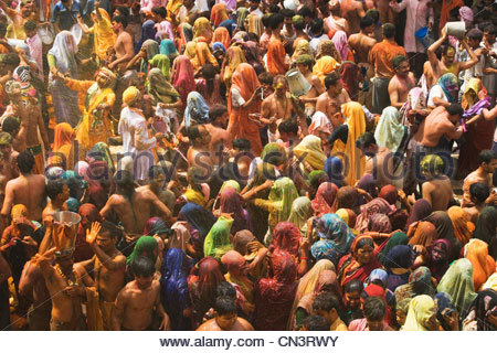A colorful crowd of people celebrate the Holi Festival, Mathura, Uttar Pradesh, India - Stock Photo